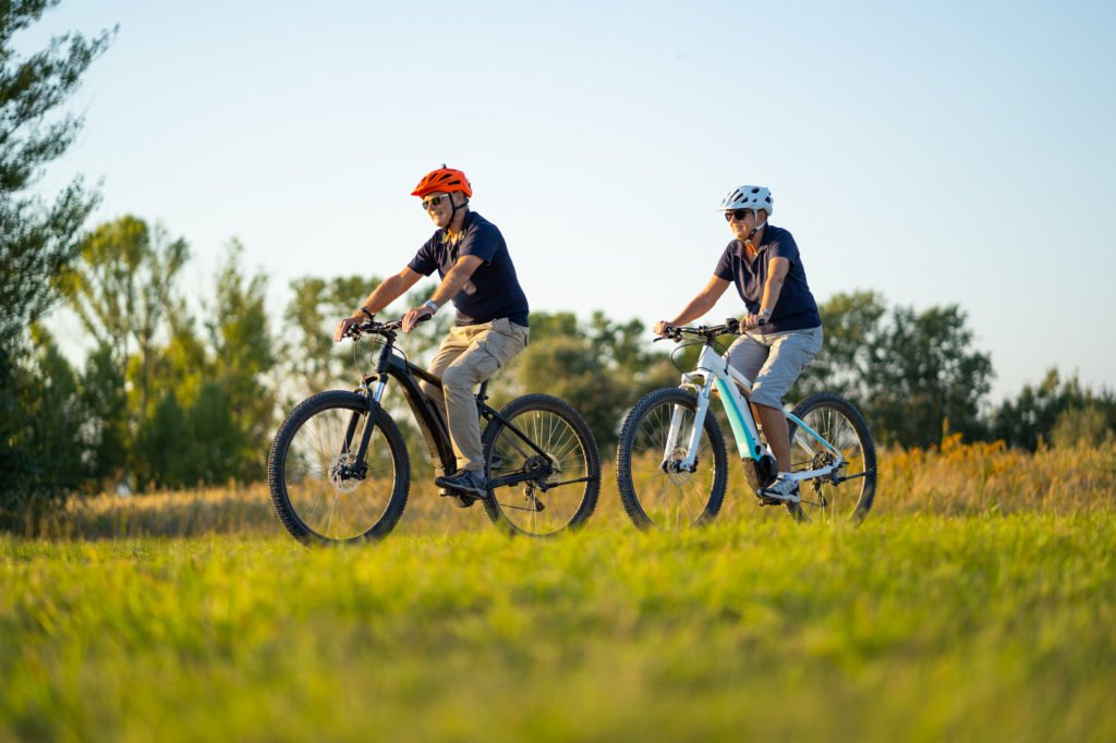 active senior couple cycling on mountain bikes through rural landscape