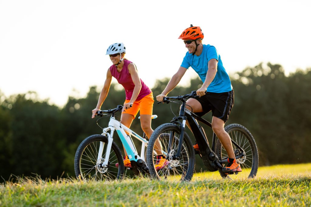 happy mature woman and man cycling together