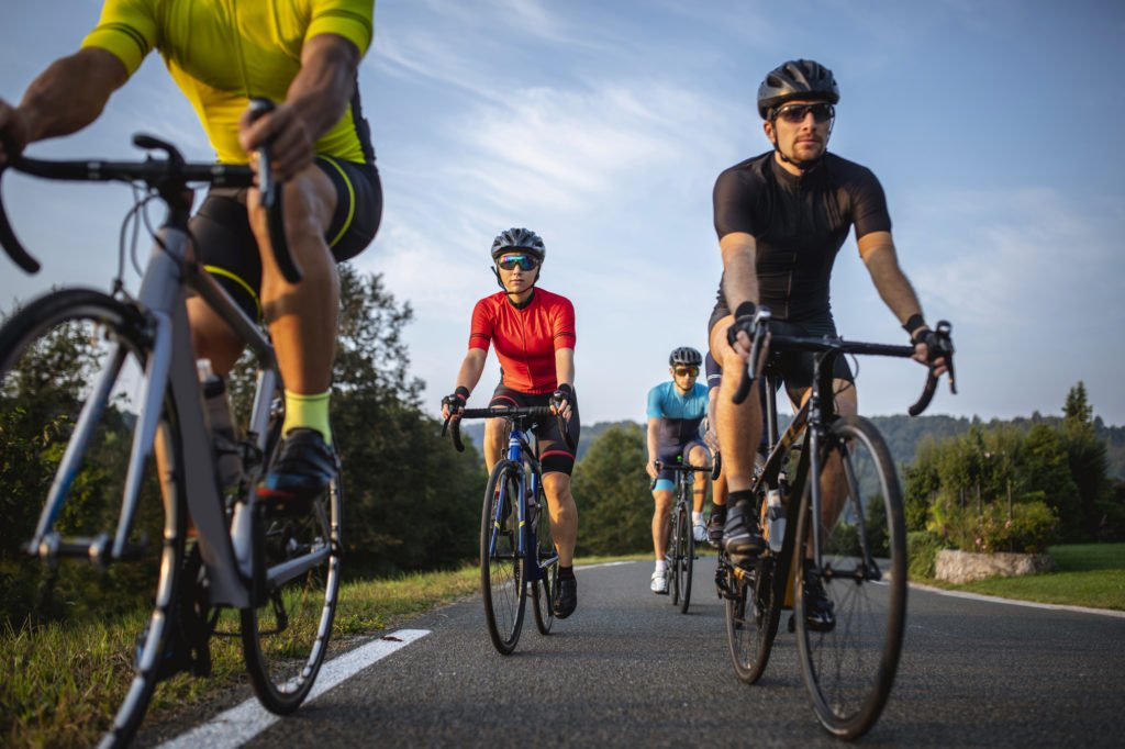 Group of Fit Cyclists Riding Mountain Road in Morning