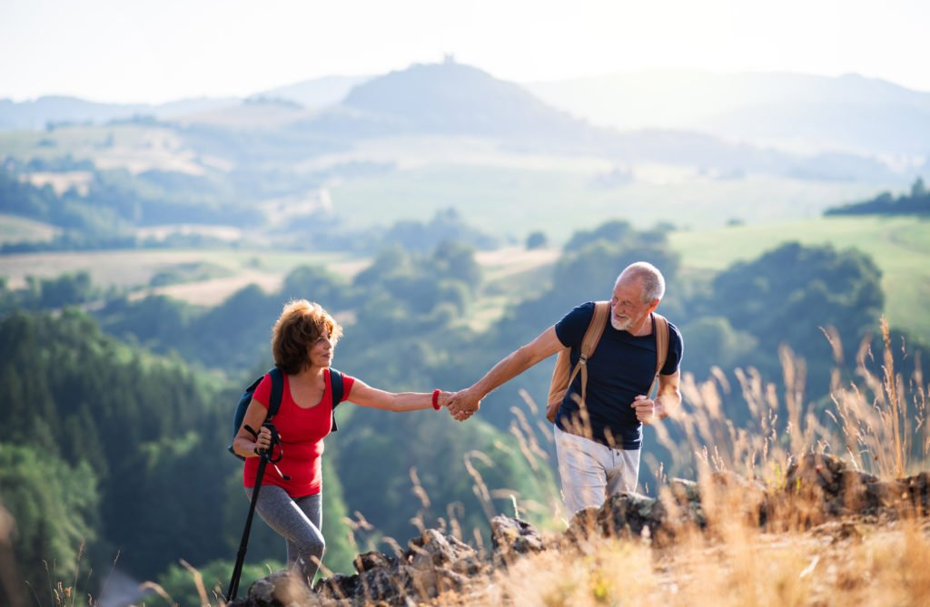 Senior tourist couple with backpacks hiking in nature, holding hands.